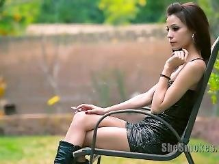 The Hot Girl In Sexy Black Mini Dress And Leather Boots Smokes A Cigarette.