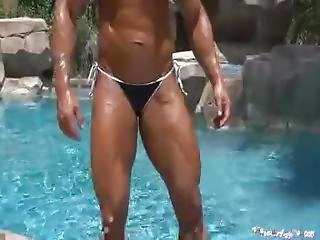 Female Bodybuilder Oiling Her Muscular And Tanned Body.