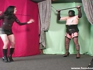 Domme In Boots Attaching Nipple Clamps On A Sissy And Whipping Him