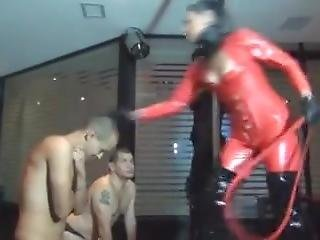 Mistress With Latex Catsuit & Boots High Heels Whipping Her Slaves