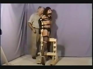 Struggling Redhead In Armbinder Gagged & Locked Into Frame