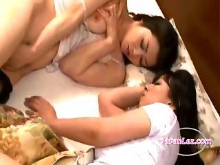 Asian Woman Patting Her Girlfriend Masturbating Next To Her On The Bed In The Bedroo
