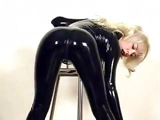 Blonde In Shiny Black Latex Catsuit