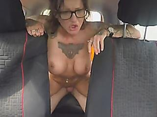 A Sexy Brunette Tattooed Girl With Glasses Gets Her Pussy Drilled In The Car