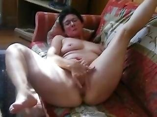 Black Haired Mature Masturbating On Couch.