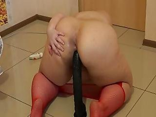 A Fat Girl In Red Pantyhose Jumps On A Black Rubber Dick