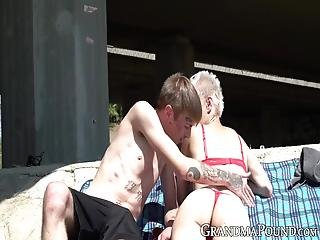 Looks Like A Handsome Older Lady Cannot Even Sunbathe Anymore Without Being Offered To Suck Off Naughty Young Men!