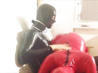 Rubber Couple: Evening Relax In Latex Catsuit On The Sofa