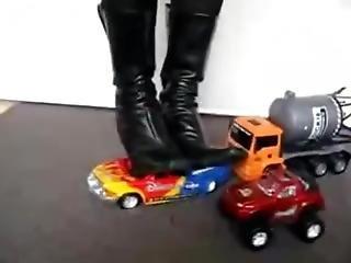 Black High Heeled Boots Crushing Three Toy Trucks