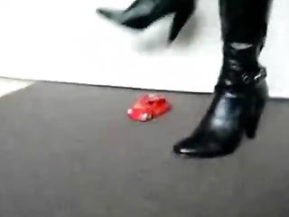 Black High Heeled Boots Crushing A Beetle Toy Car